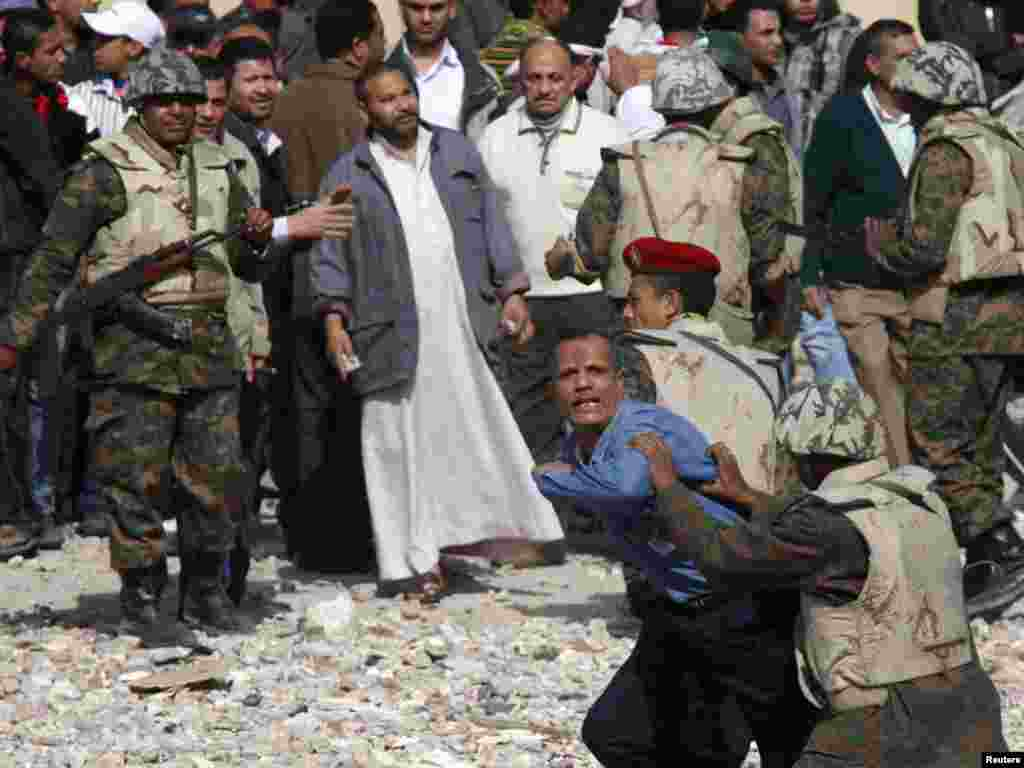 Egypian soldiers restrain a Mubarak supporter trying to get to opposition lines near Tahrir Square.