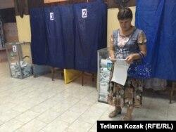 Жінка вивчає бюлетень на дільниці у Біловодську