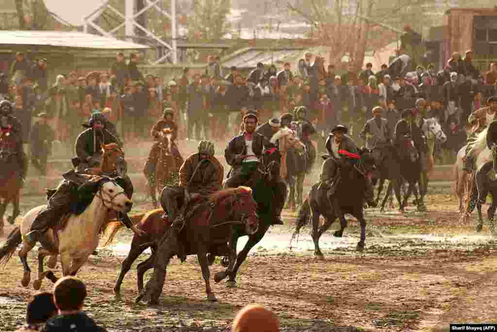Afghan horsemen compete during a game of the traditional sport of buzkashi in Badakhshan Province. The ancient game -- an Afghan national sport -- is played between two teams of horsemen competing to throw an animal carcass into a circle. (AFP/Sharif Shayeq)