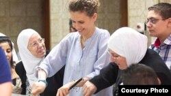 """Асма Асад Ораза айында мұқтаж жандарға тамақ таратып тұр. Instagram желісіндегі """"Сирия президенті"""" парағында жарияланған сурет."""