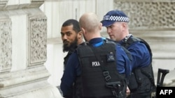Лондонские полицейские уводят вооруженного ножами мужчину.