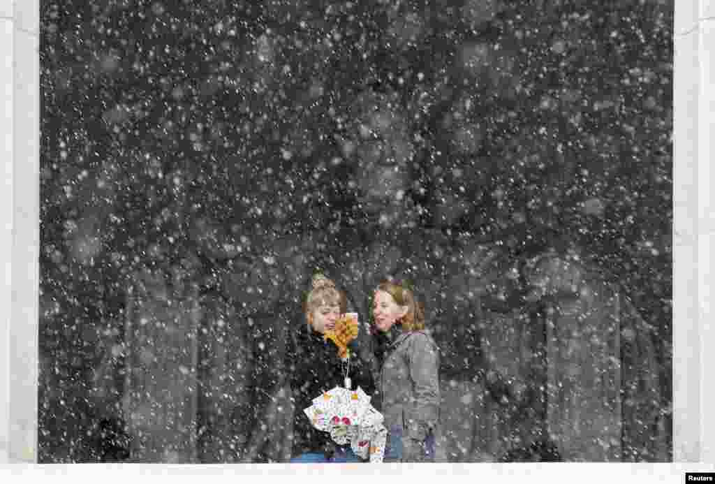 Women take pictures at the Lincoln Memorial during a snowstorm in Washington, D.C. (Reuters/Joshua Roberts)