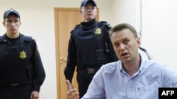 Russian opposition leader Aleksei Navalny speaks to journalists after a hearing in a Moscow court on June 12.