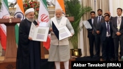 Indian Prime Minister Narendra Modi (R) and the Iranian President Hassan Rouhani releasing the commemorative stamp celebrating India-Iran relations at Hyderabad House in New Delhi on Saturday February 17, 2018.