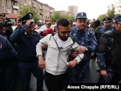 A young protester is led away by police on April 20.