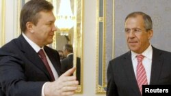 Russian Foreign Minister Sergei Lavrov (right) has urged the opposition to fulfill its part in a deal concluded with Ukrainian President Viktor Yanukovych (left) on February 21.