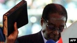 Президент Зимбабве Роберт Мугабе приводится к присяге с Библией в руках в ходе инаугурации в Хараре. 22.09.2013