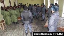 Қырғыздар мен қытай жұмысшылары төбелескен ғимаратта жүрген полицейлер. Куршаб ауылы, Ош облысы. 9 қаңтар 2013 жыл.