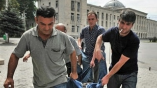 Men carry the body of a man killed by a shell in the town of Gori on August 12