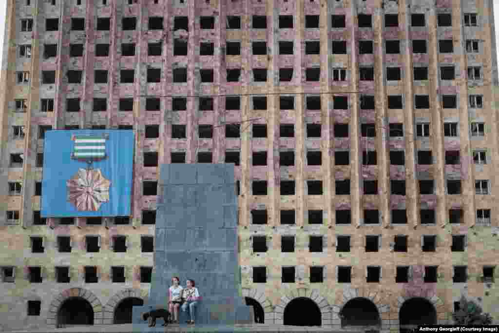 Two girls walk a dog in front of the abandoned Soviet-era government building in downtown Sukhumi. The area was the site of fierce battles in the 1992-1993 conflict.