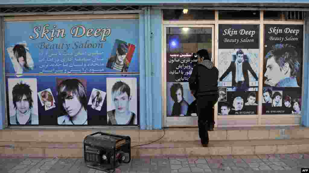 A young man enters a barber shop in Kabul in January.