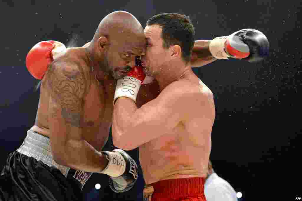 Wladimir Klitschko of Ukraine (right) punches Tony Thompson from the United States during a successful defense of his IBF, WBA, and WBO world heavyweight boxing titles on July 7. (AFP/Fabrice Coffrini)