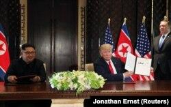 Президент США показывает документ, который он подписал с Ким Чен Ыном