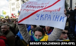 "A Ukrainian woman holds a placard denouncing any agreements with the ""enemy"" during a rally outside the presidential office in Kyiv earlier this month."