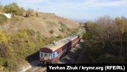 Локомотив тянет куда-то старый пассажирский вагон