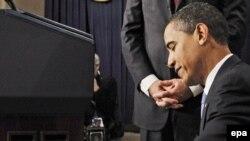Барак Обама қызметке кіріскен бірінші күні президент ретінде алғашқы құжатқа қол қоюда.