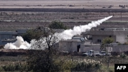 Islamic State militants fire a rocket toward People's Protection Units (YPG) fighters' positions from east of Kobani on November 6.