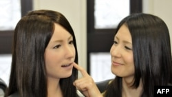 یک انسان (سمت راست) در حال لمس کردن صورت انساننمای «جیمینوئید-اف» (چپ)، که مدل غیر تجاری ربات جدید «اکتروئید-اف» است. اوساکا، ژاپن.