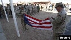 عسكري اميركي يطوي علم بلاده استعدادا للرحيل