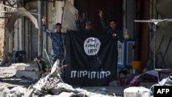 Ирачки војници го држат знамето на милитантната група ИД во знак на победа.