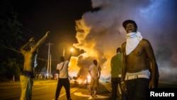 Демонстранты в Фергюсоне протестуют против убийства афроамериканца полицейским, 18 августа 2014