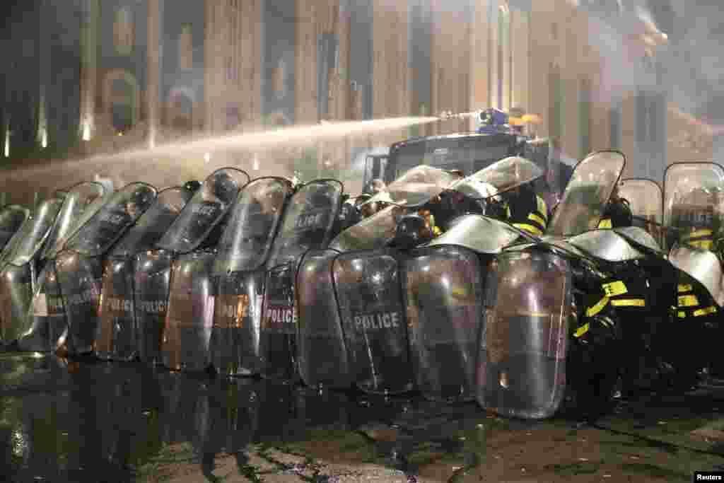 Полицейские защищаются щитами