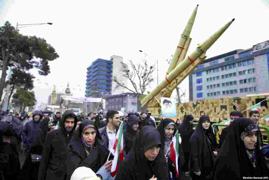 "Iranians walk past a missile during a rally in Tehran. Banners held by marchers or hung in the streets bore slogans including ""Death to America,"" ""Death to Israel,"" and ""40 years of challenge, 40 years of U.S. defeats."""