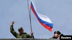 A man holds a Russian flag on the roof of the Ukrainian naval headquarters in Sevastopol on March 19.