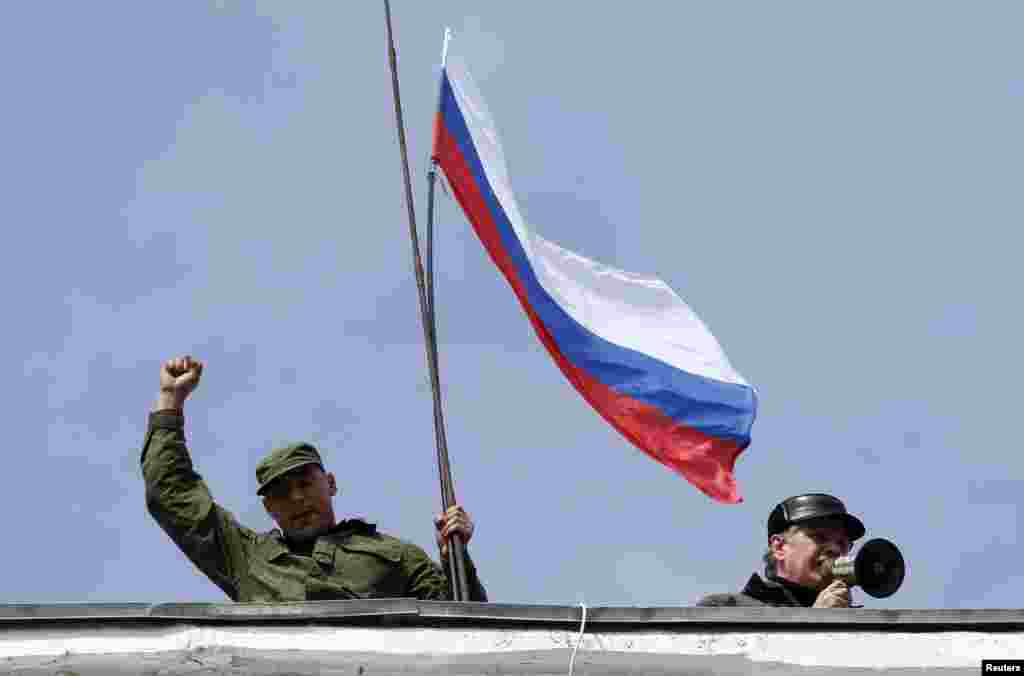 Ukraine -- A man holds a Russian flag on the roof of Ukrainian naval headquarters as another man addresses the crowd outside with a megaphone in Sevastopol, March 19, 2014