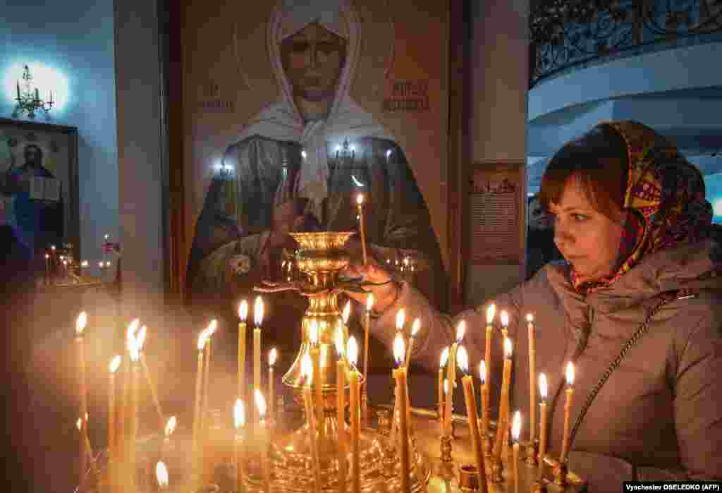 A woman lights a candle in a church in Bishkek on January 7, when Orthodox Christians celebrate Christmas in the Middle East, Russia, and other Orthodox churches that use the old Julian calendar instead of the 17th-century Gregorian calendar adopted by Catholics, Protestants, Greek Orthodox, and commonly used in secular life around the world. (AFP/Vyacheslav Oseledko)