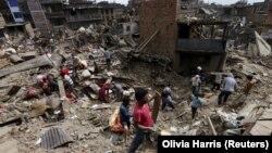 Banorët lokalë i pastrojnë mbeturinat në shtëpitë e tyre pas tërmetit