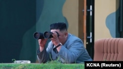 NORTH KOREA -- North Korean leader Kim Jong Un watches the test-fire of two short-range ballistic missiles at an undisclosed location, July 25, 2019