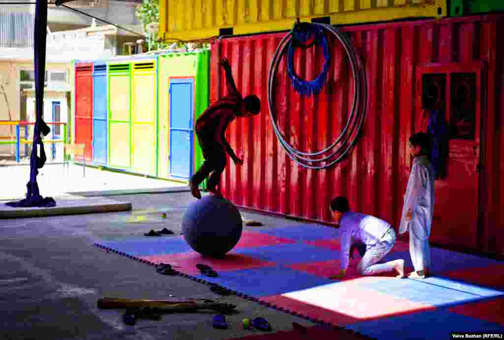 A child practices balancing on a ball. Students are taught acrobatics, tight rope, and juggling.