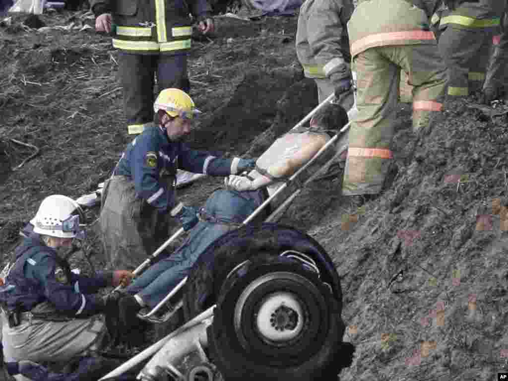 Rescue workers remove a body from the crash site.