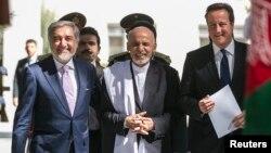 Britain's Prime Minister David Cameron walks with Afghanistan's President Ashraf Ghani (C) and Abdullah Abdullah.