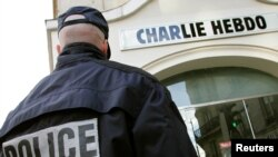 A policeman stands guard outside the French satirical weekly Charlie Hebdo office in Paris (file photo).