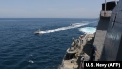 This photo obtained from the U.S. Navy on April 15 shows what it says are IRGC vessels conducting unsafe actions against U.S. military ships by crossing the ships' bows and sterns at close range while operating in international waters. Iran disputes that version of events.