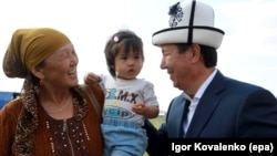 The leader of the Ak-Shumkar party, presidential candidate Temir Sariev (right), meets with local residents during his election campaign event in the village of Kun-tuu, near the capital of Bishkek, on September 11.