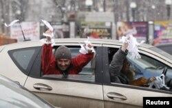 Сторонники оппозиции показывают белые ленточки из проезжающей машины. Москва, 26 февраля 2012 года.