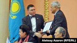 Генеральный консул США Марк Муди (слева) вручает директору архива президента Казахстана Борису Джапарову копию письма президента Буша от 26 декабря 1991 года о признании независимости Казахстана. Алматы, 8 декабря 2016 года.