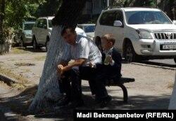 Мектеп қасында отырған оқушы мен ересек адам. Алматы, 3 қыркүйек 2013 жыл.
