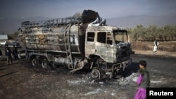 Afghanistan -- A boy walks past a burnt fuel tanker in Parwan province.