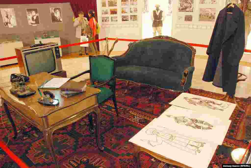 На подиуме воссоздан рабочий кабинет Шакена Айманова – письменный стол, кресло, диван, телевизор, вешалка с пальто. На столе – канцелярские принадлежности, телефонный аппарат. Все эти и большинство других экспонатов предоставила киностудия «Казахфильм».