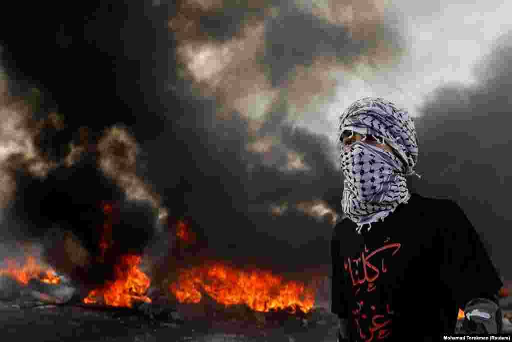 A Palestinian demonstrator looks on as tires burn during a protest against U.S. President Donald Trump's Middle East peace plan, near the Jewish settlement of Beit El in the West Bank on January 30. (Reuters/Mohamad Torokman)