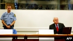 The late Yugoslav ex-President Slobodan Milosevic (right) on trial at The Hague in 2004