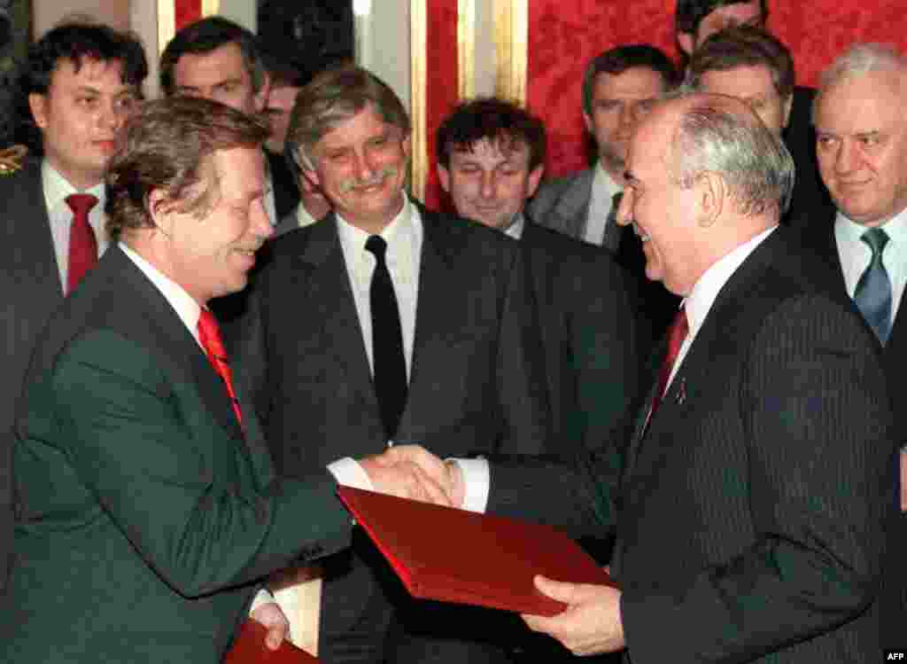 Czechoslovak President Vaclav Havel shakes hands with Gorbachev as they exchange documents on the withdrawal of Soviet troops in Moscow on February 26, 1990.