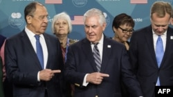 U.S. Secretary of State Rex Tillerson (center) shows the way out to Russian Foreign Minister Sergei Lavrov (left) after posing for a family photo at the Arctic Council meeting in Fairbanks, Alaska, on May 11.