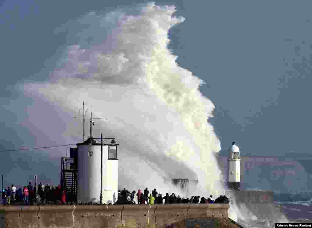 Waves crash over a lighthouse as Ophelia, a former Atlantic hurricane, passes Porthcawl, Wales, on October 16. (Reuters/Rebecca Naden)