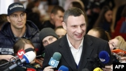 With his brother Vladimir in the background, Kyiv Mayor Vitali Klitschko speaks to the media after casting his ballot during the second round of the municipal election in Kyiv.