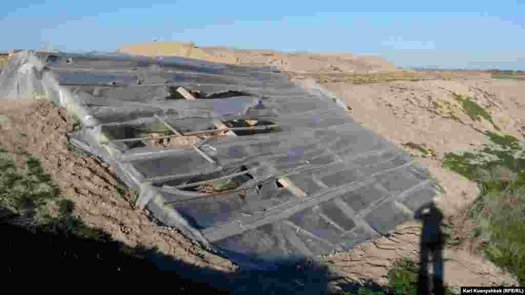 Қамалдың реставрация жүргізуге дайындалған бөлігі. Қатты соққан жел салдарынан археологтардың жабын ретінде пайдаланылған полиэтилені жыртылған.